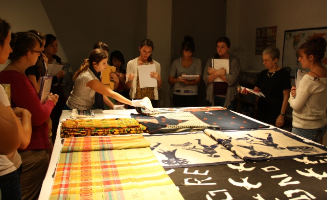 Students standing around a table looking at colorful textiles