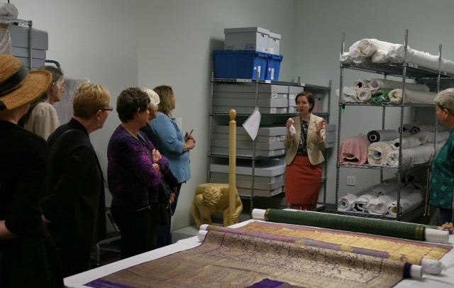 Mary Hauser shows visitors some textiles